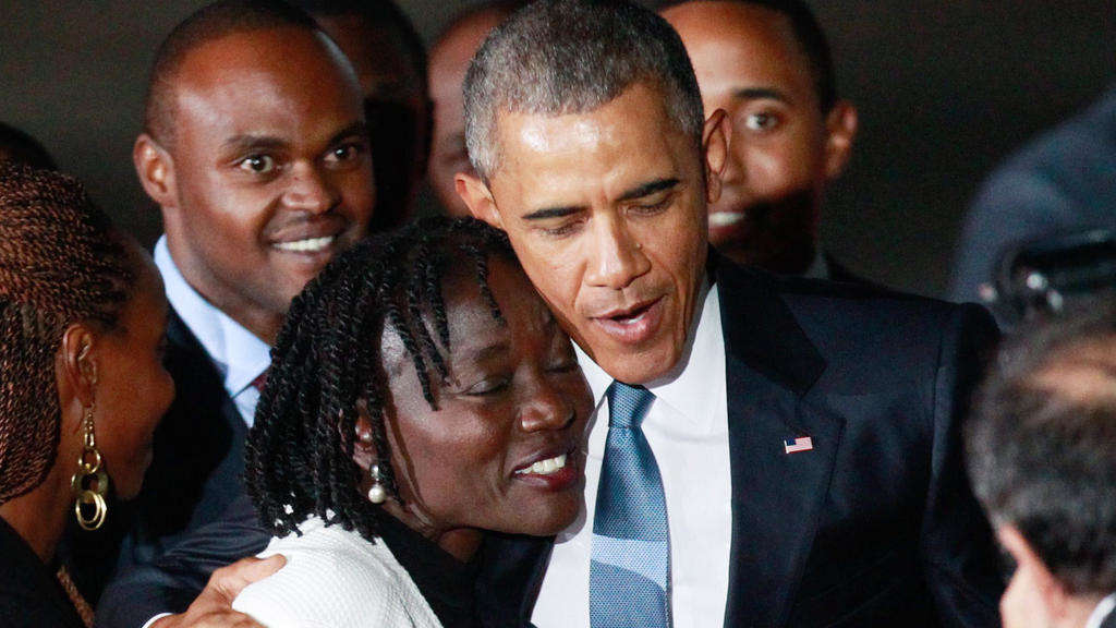 Foto: US-Präsident Barack Obama (2. v. r.) umarmt seine Halbschwester Auma Obama (3. v. l.) am Jomo Kenyatta International Airport.